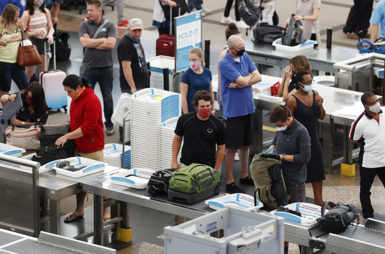 Image: Travelers move through a security checkpoint at Denver International Airport