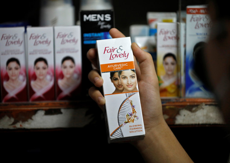 """A customer picks up a \""""Fair and Lovely\"""" skin lightening product in a shop in Ahmedabad, India, on June 25, 2020."""