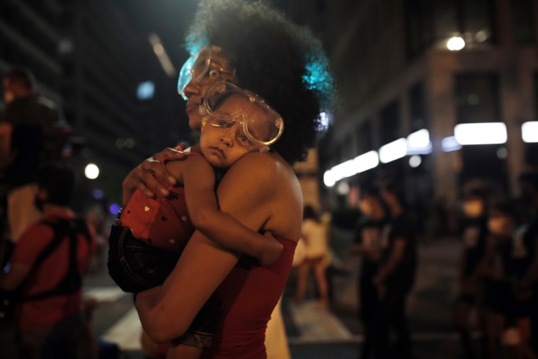 A sleepy Bonita wears protective goggles as she settles into her mother's shoulder during a protest near the White House on June 23.