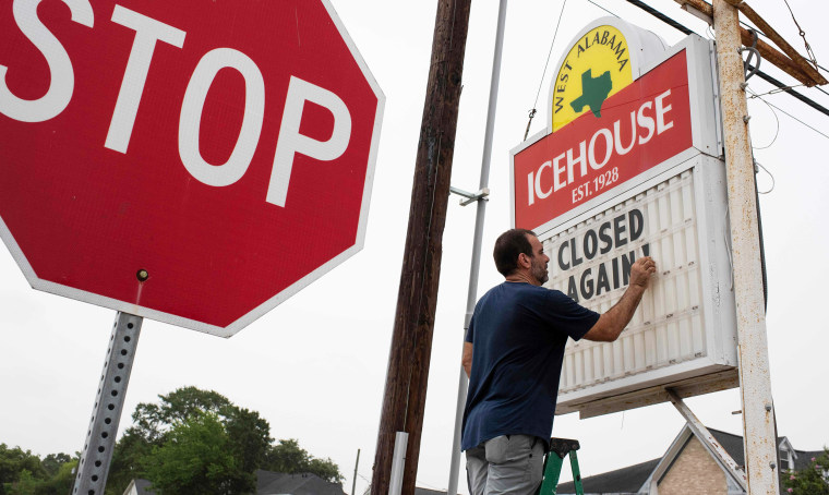 """Image: A bar owner changes the marquee outside his bar to \""""Closed Again\"""" at the West Alabama Ice House in Houston"""