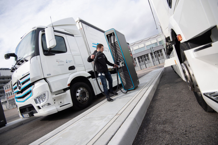 A Daimler AG employee holds a charging plug next to an electric powered Mercedes-Benz eActros in Stuttgart, Germany, on Feb. 18 2020.