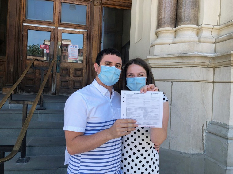 The bride and groom with their marriage license.