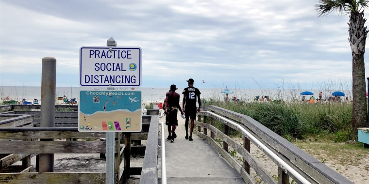 A sign asks people to maintain social distancing on the beach in Myrtle Beach, S.C., on June 18, 2020.