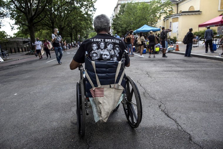 A wheelchair-bound man wearing a t-shirt with I can't
