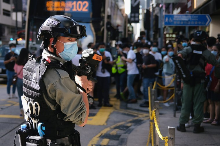 Image: A riot police officer holds a pepper spray projectile as he stands guard to stop a mass gathering during a protest in Hong Kong.