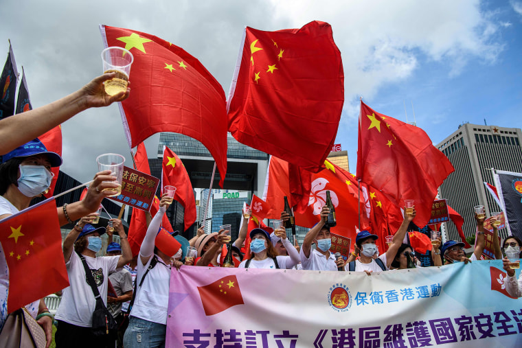 Image: Pro-China supporters display Chinese and Hong Kong flags as they raise a toast with champagne during a rally near the government headquarters in Hong Kong