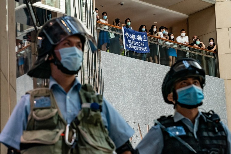 Image: Pro-democracy supporters hold a Hong Kong Independence flag and shout slogans during a rally against the national security law as riot police secure an area in a shopping mall