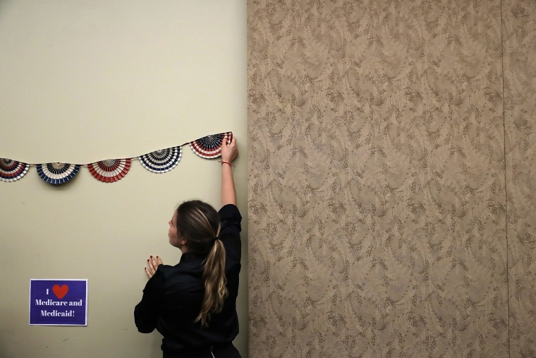 Image: House Democratic caucus staff members prepare a background for photographs before an event to celebrate the 52nd anniversary of Medicaid and Medicare at the Capitol.