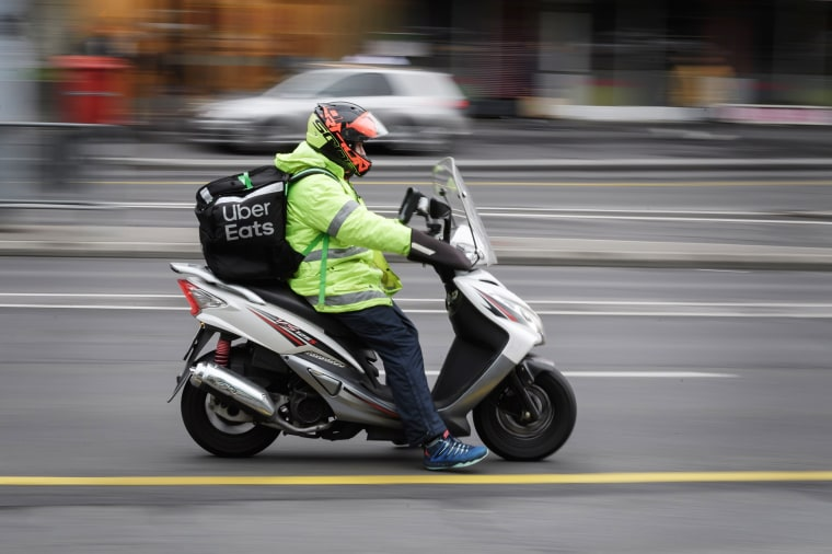 Image: An Uber Eats delivery person rides a scooter in a street in Lausanne