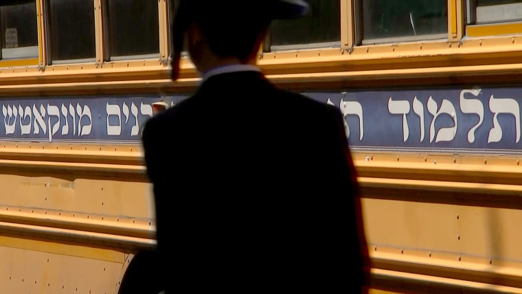 An Orthodox Jewish man walks in front of a school bus in the predominantly Hasidic neighborhood of Borough Park in Brooklyn, N.Y.