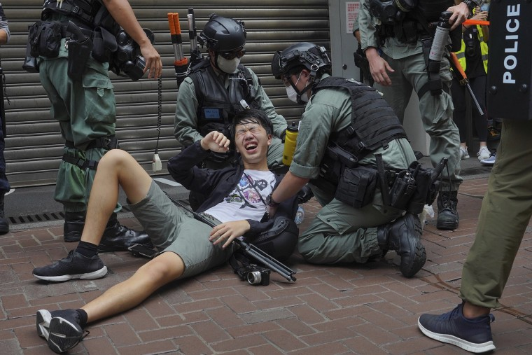 Image: A reporter falls down after being sprayed with pepper spray by police during a protest in Causeway Bay during the annual handover march in Hong Kong
