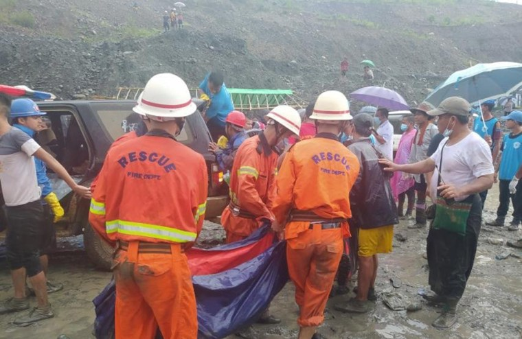 Image: Rescue workers carry a dead body following a landslide at a mining site in Hpakant, Kachin State City, Myanmar