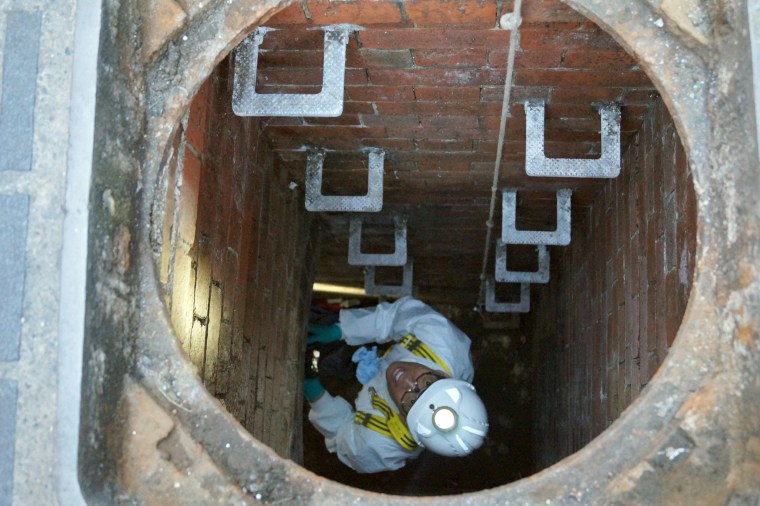 Image: A water company worker climbs down into a sewage pipe in London.