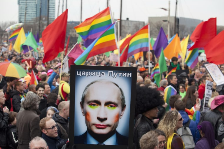 A demonstrator holds up a picture depicting Russian President Vladimir Putin with make-up during a protest by the gay community in Amsterdam on April 8, 2013.