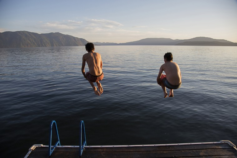 Boys jumping into lake from dock