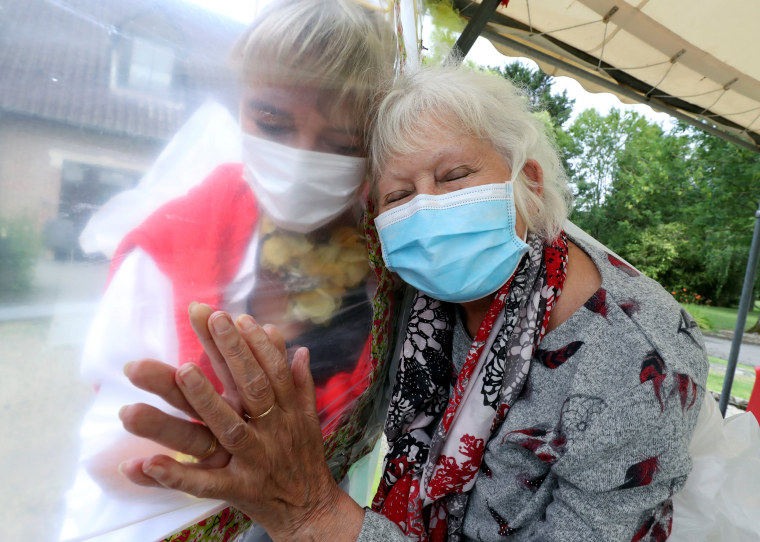 """Image: Residents at Belgian nursing home \""""Le Jardin de Picardie\"""" enjoy hugs and cuddle through a wall made with plastic sheets to protect against potential COVID-19 infection in Peruwelz"""