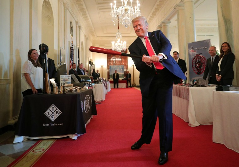 """Image: President Trump swings a wooden baseball bat as he attends a \""""Spirit of America Showcase\"""" event in the Cross Hall of the White House in Washington"""