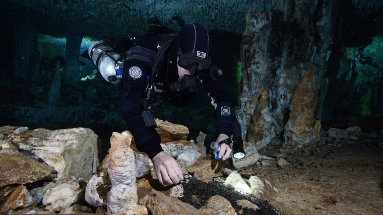 Image: A diver takes charcoal samples in the Sagitario cave in Mexico's Yucat?n region, the site of the oldest ochre mine found in the Americas.