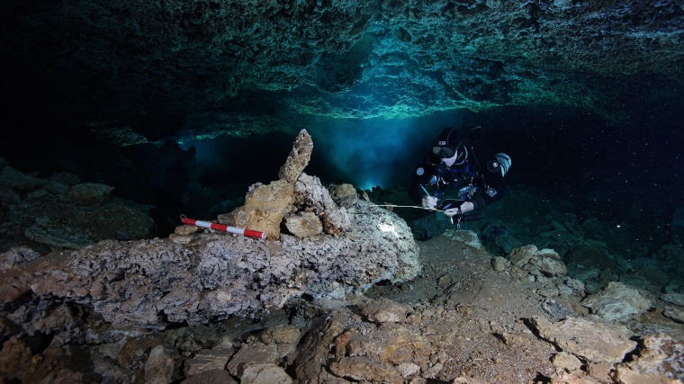 Image: A diver examines a navigational landmark in the now-flooded cave, left by ancient ochre miners more than 10,000 years ago.