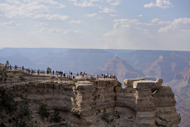Image: Visitors stand on an observation deck at Mather Point of Grand Canyon National Park in Grand Canyon, Arizona.