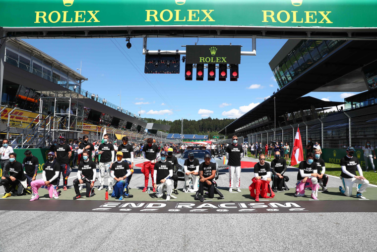 """Image: Drivers kneel behind a banner reading \""""End racism\"""" ahead the Austrian Formula One Grand Prix race on July 5, 2020 in Spielberg, Austria i"""