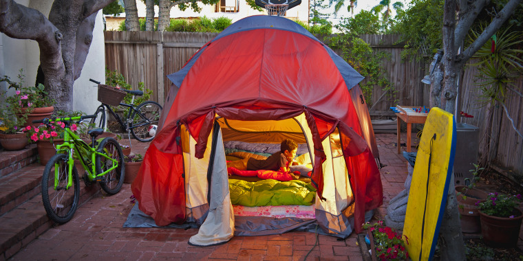 boy reading in tent in side yard of house