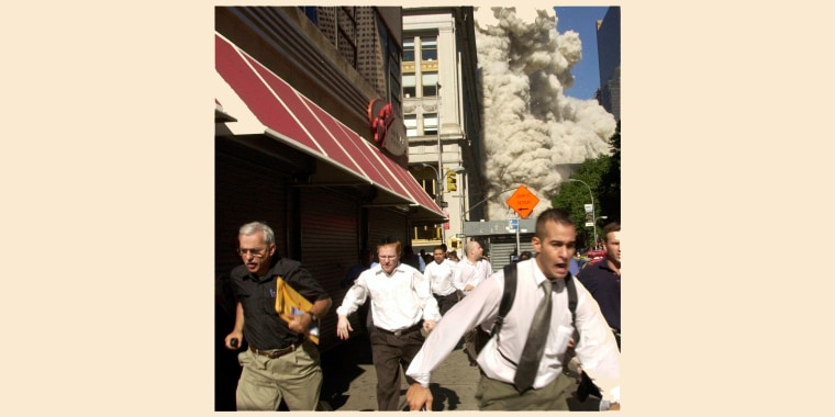 In this Sept. 11, 2001, file photo, people run from the collapse of one of the twin towers at the World Trade Center in New York. Stephen Cooper, far left, can be seen fleeing smoke and debris as the south tower crumbled just a block away. Cooper died from the coronavirus this year, his family said.