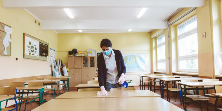 A teacher wipes down desks in a classroom before students return to school during the coronovirus pandemic.