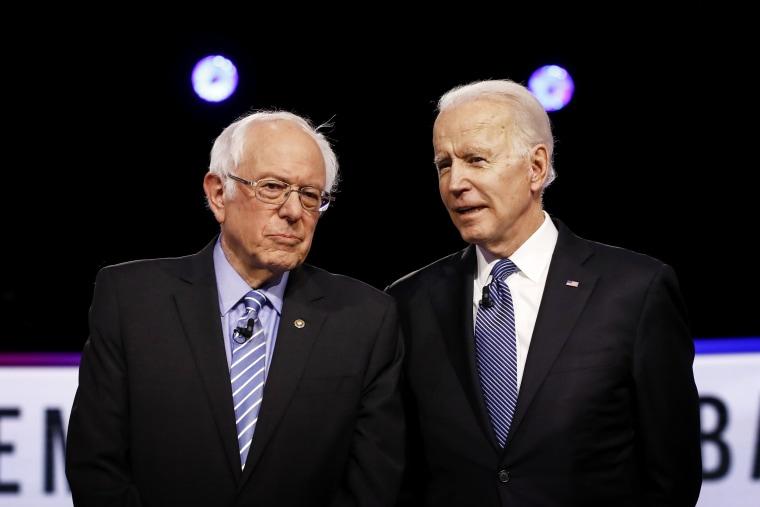 Image: Sen. Bernie Sanders and Joe Biden speak before a Democratic presidential primary debate in Charleston, S.C., on Feb. 25, 2020.