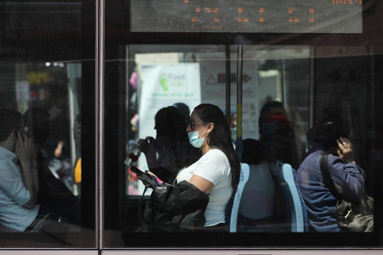 Image: Passengers, one wearing a protective mask, are seen through the windows of the light rail in Jerusalem amid the spread of the coronavirus disease (COVID-19)