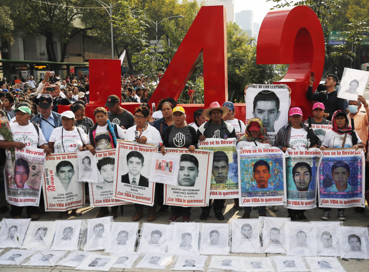 Relatives of 43 missing college students hold posters with the photos of their loved ones as they protest on the fifth anniversary of the students' disappearance in front of a monument in their memory in Mexico City on Sept. 26, 2019.