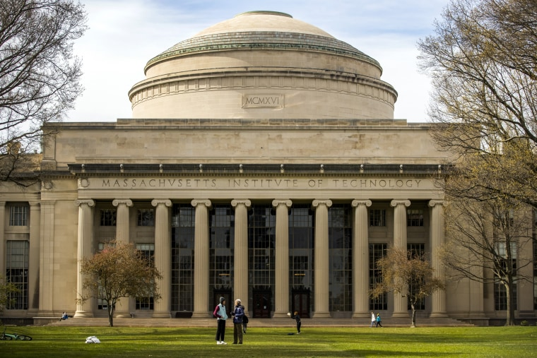 People stand on the Massachusetts Institute of Technology campus in Cambridge, Mass., on April 20, 2020.