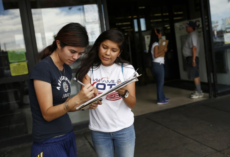 Mi Familia Vota volunteer Fabiola Vejar, right, registers Stephanie Cardenas to vote in front of a Latino supermarket in Las Vegas on June 9, 2016.