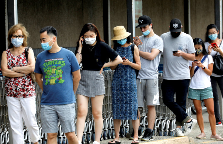 Image: People wear protective face masks outside at a shopping plaza in Edgewater, New Jersey