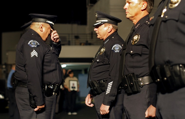 Sgt. Enrique Gonzalez is overcome with emotion as before handing over his police badge to Maywood P