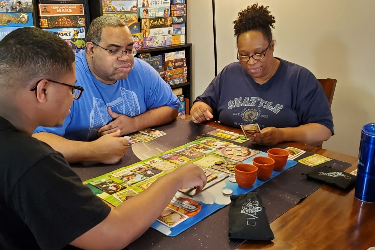 """""""Mik"""" Fitch, center, his wife Starla and son Grant play the board game Chai."""