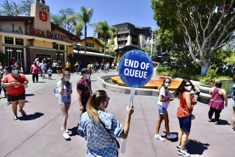 A Disney employee runs a line to get in to the virtual queue for the World of Disney on the reopening day of the Downtown Disney District in Anaheim, Calif., on July 9, 2020.