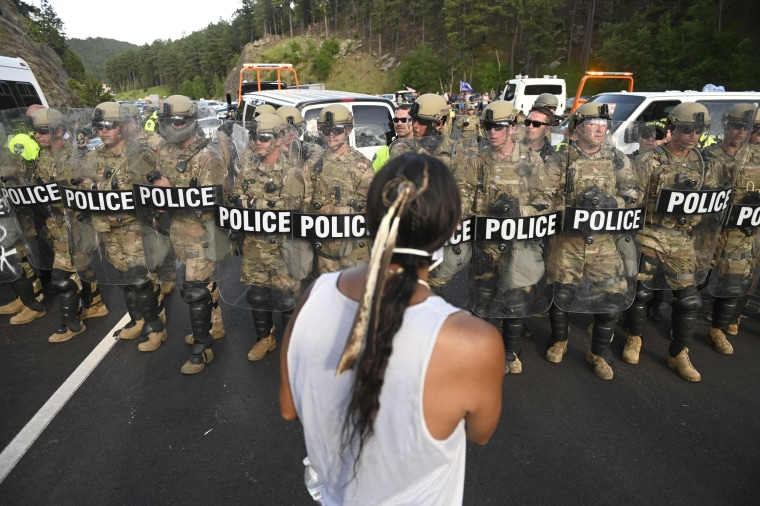 A man faces a row of police as activists and members of different tribes from the region block the road to Mount Rushmore National Monument in Keystone, S.D., on July 3, 2020.