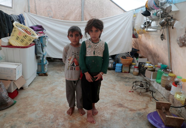 Image: Displaced Syrian twins from east Idlib, pose for a picture in a tent at Atmeh camp