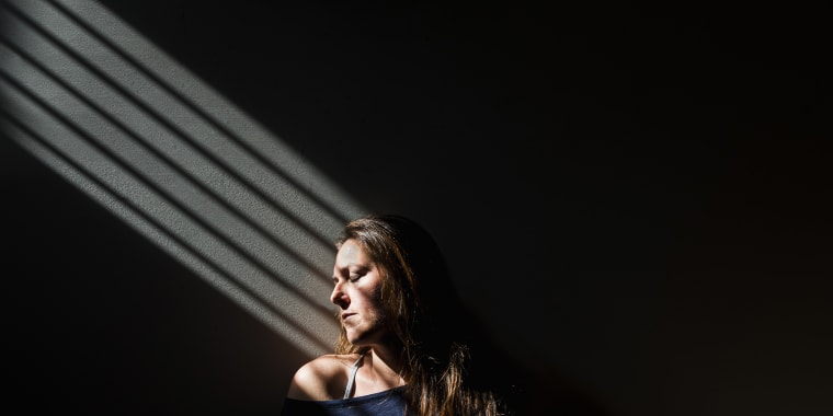 Profile of a woman sitting in a patch of light in a darkened room.