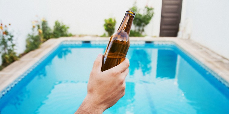 Cropped Hand Holding Bottle Against Swimming Pool