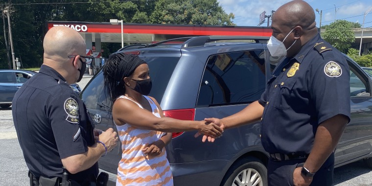 A police officer shakes hands with a woman who received a gift card for groceries, courtesy of Tyler Perry.