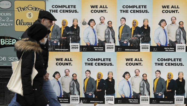 Image: People walk past posters encouraging participation in the 2020 Census in Seattle