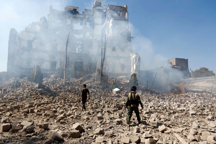 Image: Huthi rebel fighters inspect the damage after a reported air strike carried out by the Saudi-led coalition targeted the presidential palace in the Yemeni capital Sanaa.