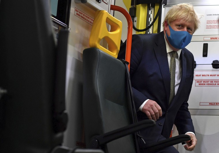 Image: Britain's Prime Minister Boris Johnson, wearing a face mask, boards an ambulance during a visit to the headquarters of the London Ambulance Service NHS Trust in London