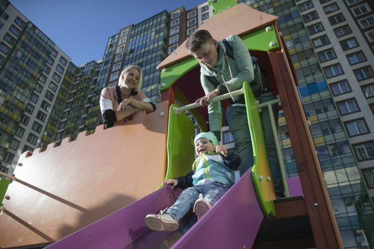 Irina, left, and Anastasia Lagutenko play with their son, Dorian, at a playground in St. Petersburg, Russia on July 2, 2020.