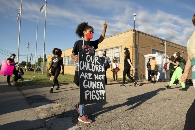 Demonstrators block the driveways of a Detroit school bus terminal to keep buses from running on the first day of summer classes on Monday.