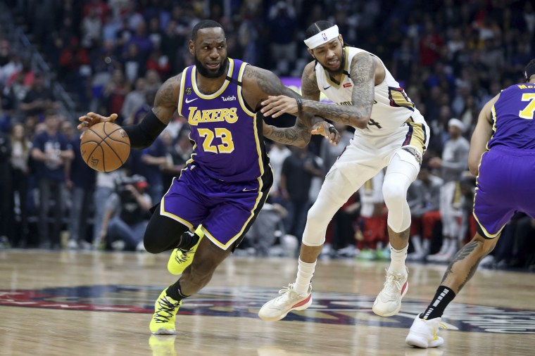 Los Angeles Lakers forward LeBron James (23) dribbles the ball past the defense of New Orleans Pelicans forward Brandon Ingram (14) in the first half of an NBA basketball game in New Orleans on March 1, 2020.