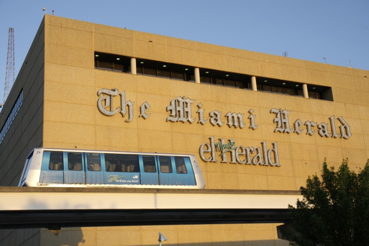 Image: A metromover passing the Miami Herald Plaza building.