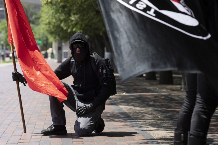 Image: Anti-fascist protesters hold flags on the Christian Science Plaza, Saturday, July 11, 2020, in Boston.